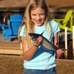 Excited young girl holding a catfish
