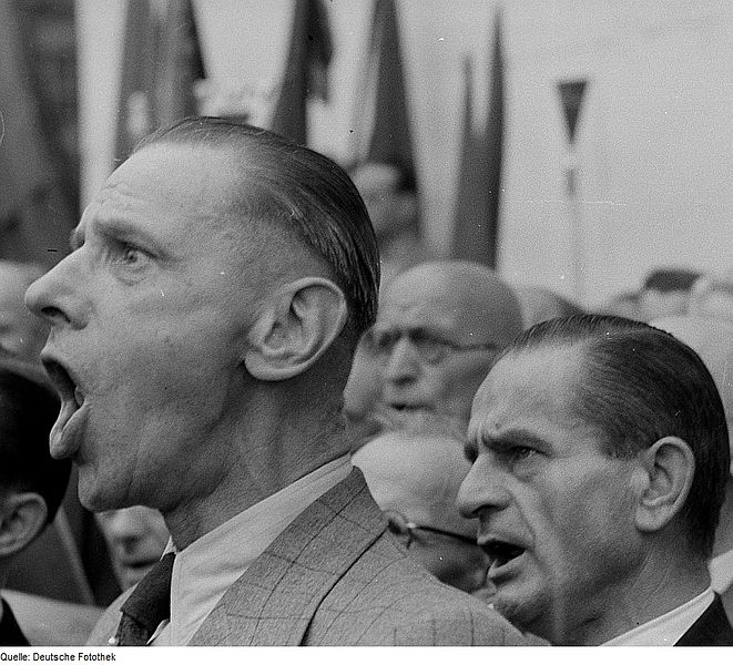"""Singende Teilnehmer auf der """"Opfer des Faschismus - Friedenskundgebung"""" from Deutsche Fotothek. Image via Wikimedia Commons. CC license 3.0."""