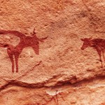 Ancient rock paintings in Sahara Desert, Tadrart, Algeria by Pichugin Dmitry. Image via Shutterstock.