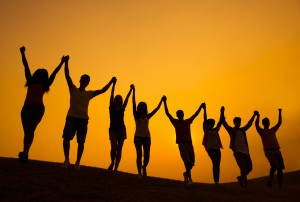 people raising their arms in triumph silhouetted by the setting sun