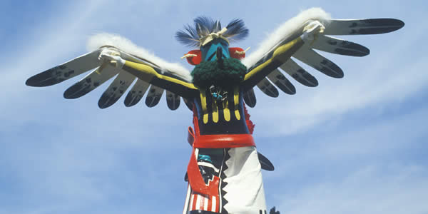 Hopi Kachina doll with outstretched winged arms against blue sky