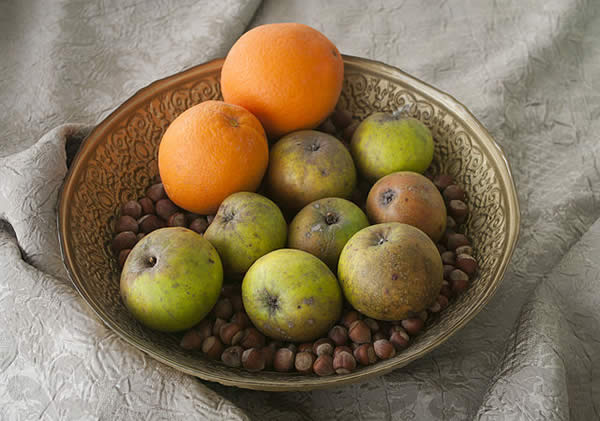 A bowl with oranges, apples, and chestnuts in it