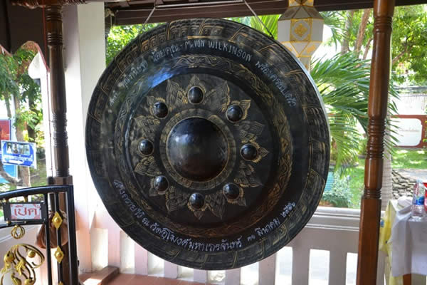 a large gong suspended from the ceiling of an outdoor porch or gazebo