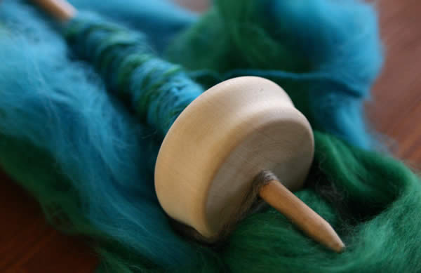 a spindle and blue-green wool