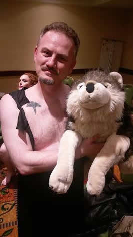 A man in a vest holding a stuffed doll of a wolf