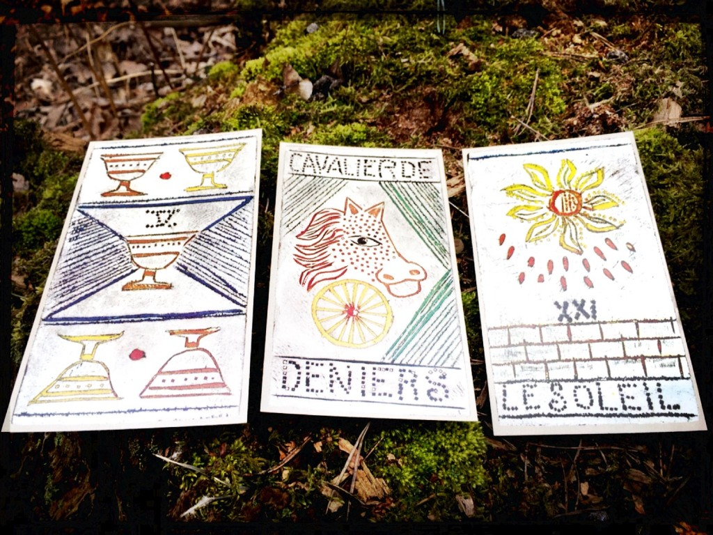 three tarot cards -- the 5 of cups, the knight of coins, and the sone -- placed on a mossy rock
