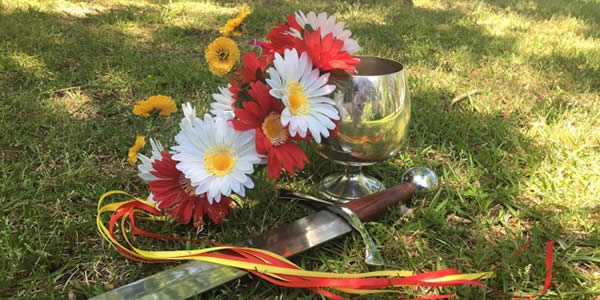 a wreath, chalice, and blade placed on the ground outside