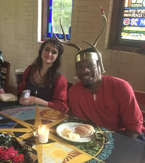 Our MayQueen Joy Leaf, and May King Jupiter as they sit at feast in their courtly hall with their attendants. Photo by Heron Michelle