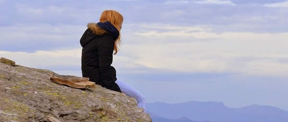 a woman sits on the edge of a cliff looking into the distance