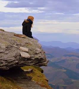 a woman sits on a cliff looking into the distance