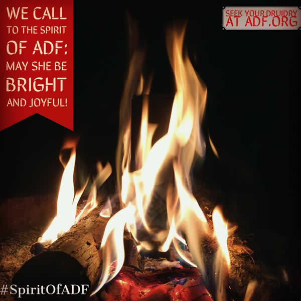 "A campfire with the following phrases around it:  (1) ""We call to the spirit of ADF: may she be bright and joyful!"" (2) ""Seek your Druidry at adf.org"" (3) ""#SpiritOfADF"""