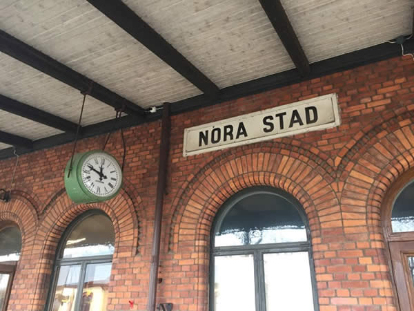 "a brick building showing an exterior clock with the Swedish phrase ""Nora Stad"" (translation: Nora Station)"
