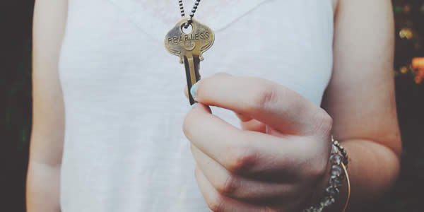 "a woman holds a key hung aruond her neck; on the key the word ""fearless"" has been stamped"