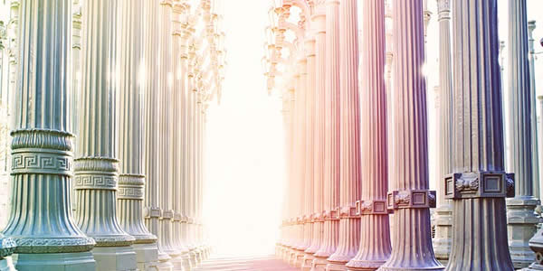 a photograph taken from within a building showing a series of columns as the sun shines into the hallway formed by them