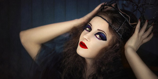 a model in makeup, including red lipstick and purple eyeshadow