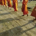 jodi-cobb-buddhist-monks-walk-single-file-down-a-dirt-road