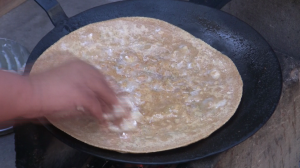 Fresh Butter on hand-made Aloo Paratha (Bread stuffed with Potato) in the Pind (Village)