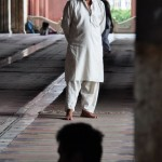 muslim man looks over a meditator at Jama Masjid, India