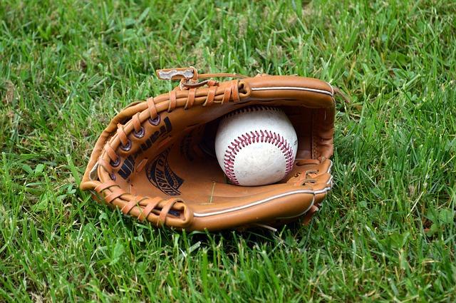 Baseball glove and ball on grass