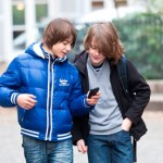 Young boys using mobile phone.