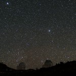 Starry night sky with two astronomical observatories in the foreground.