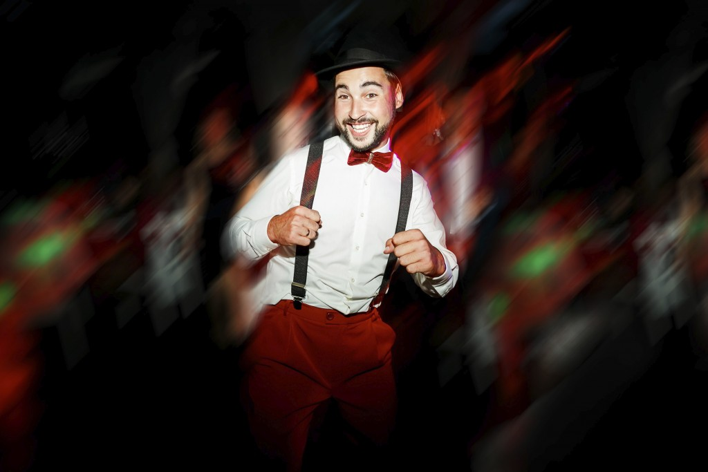 The groom dancing on dance floor, moving in motion. Cheerful man in hat, with mustache, beard and bow tie with suspenders. White shirt and red pants. Wedding color style Marsala. Having fun on party.