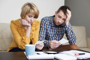Sad young couple paying bills.