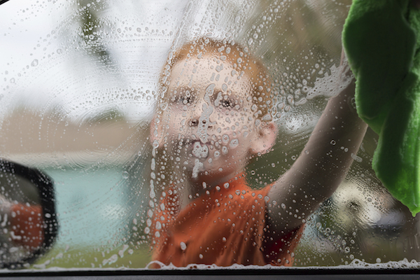 Little boy washing a car window.