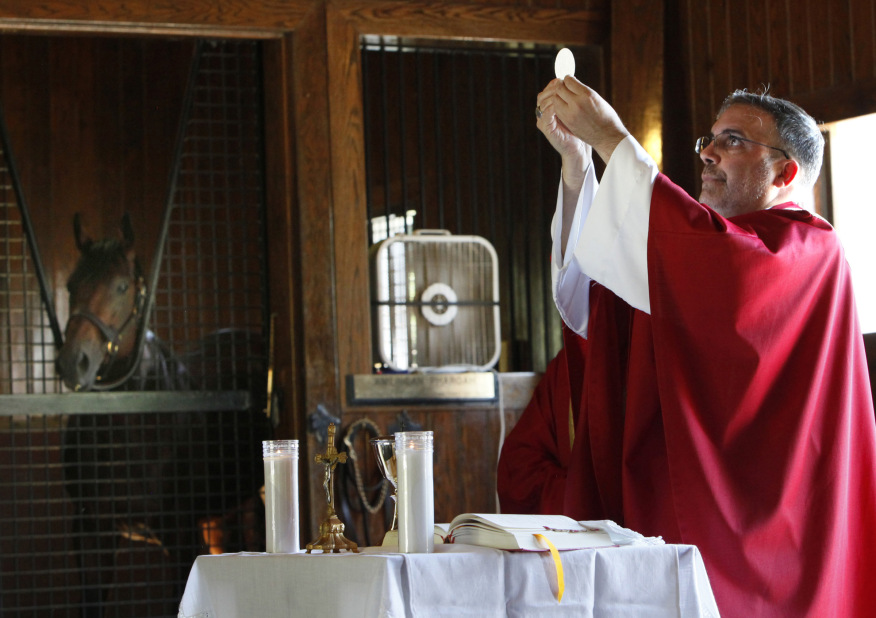 Bishop John Stowe of Lexington raises the Eucharist during Mass on Sept. 21 at Ashford Stud Farm. On the left, 2015 Triple Crown Winner American Pharoah watches Mass from his stall. The Mass was part of Chicago Auxiliary Bishop John Manz's pastoral visit to migrant workers in Kentucky on behalf of the USCCB Sept. 19-22, 2016. (Karen Callaway/Catholic New World)