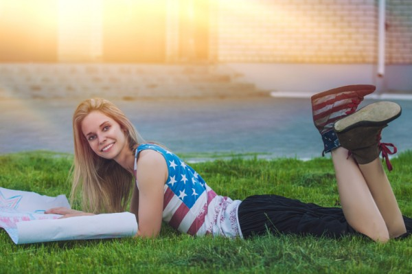 Female model against a lawn in a t-shirt with the American flag