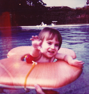 1988. Rhiannon reaches for the camera with her right hand. But shortly after this picture is taken, she has a major stroke (at three years old), leaving the right side of her body paralyzed for life.