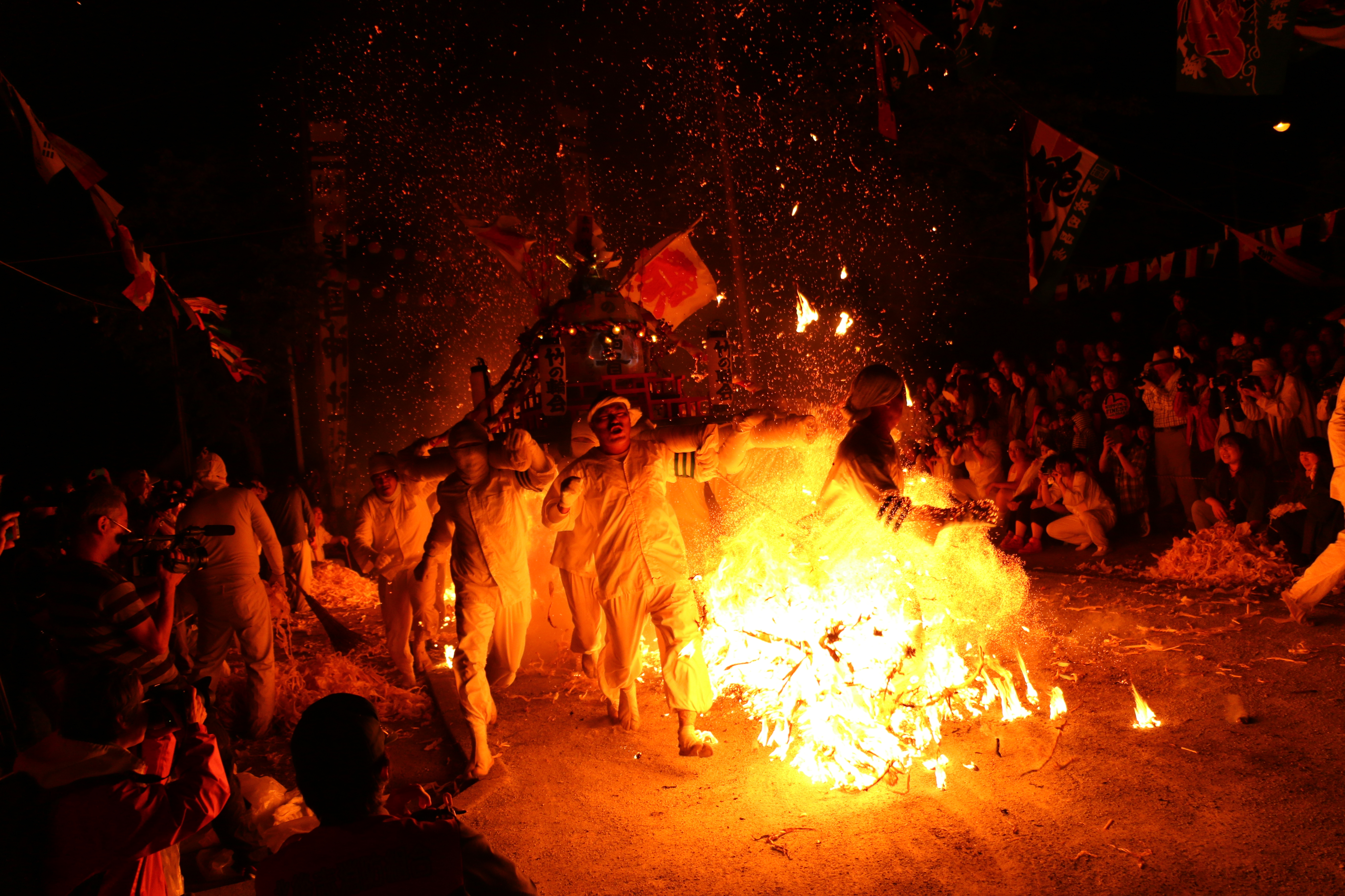 Group carrying a portable shrine through flames in Northern Japan