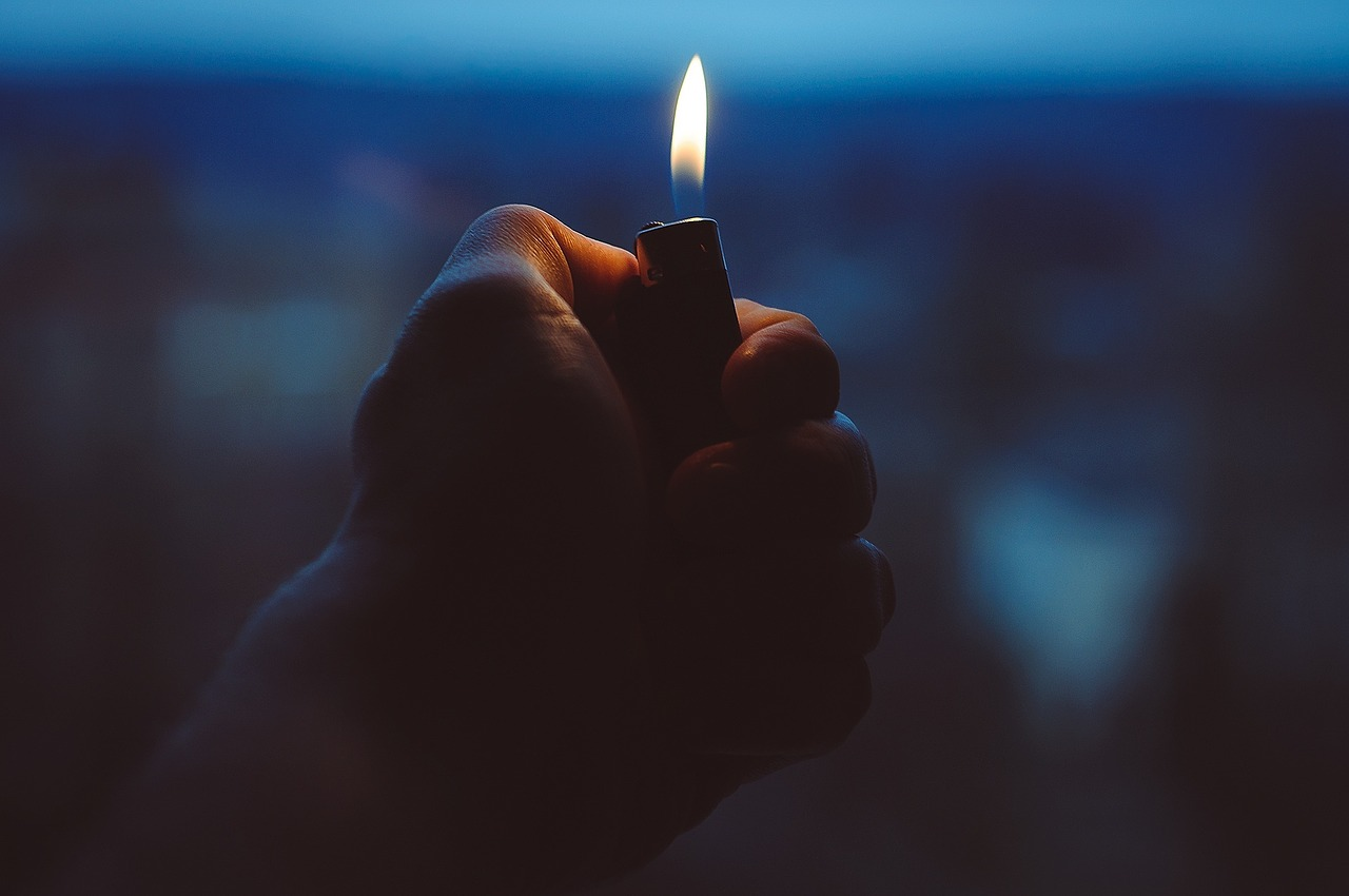 A hand holding a lit lighter