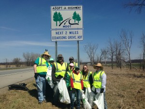 a group of druids holding filled trash bags along the expressway, under the road sign with their name on it.