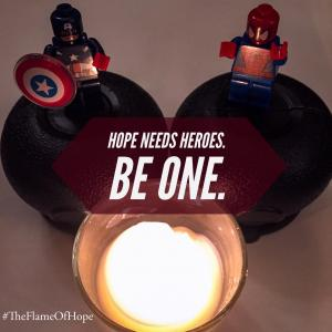 a candle lit in front of two lego superhero minifigs with the words Hope Needs Heroes. Be one.