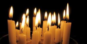 Many candles burning in a group with a dark background.