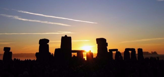 An image of Winter Solstice at Stonehenge with the sun just rising over the stones.