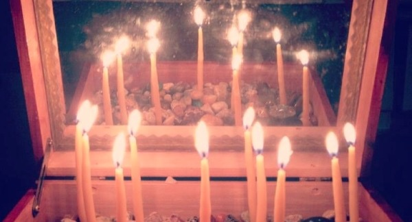 a box with candles lit within it reflecting in a mirror in the box lid to make a circle of candles.