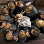 Blessing a baby: Men who have been ordained to the Melchizedek priesthood each hold the baby up with one hand while the other hand is placed on the shoulder of the man to the left, forming a symbolic circle of shared support. (Click to enlarge.)