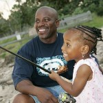 A father teaching his daughter how to fish