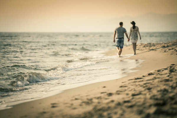 couple holding hands beach