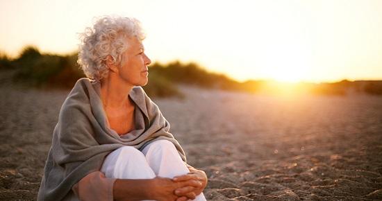 Woman sitting at sunset 550x290