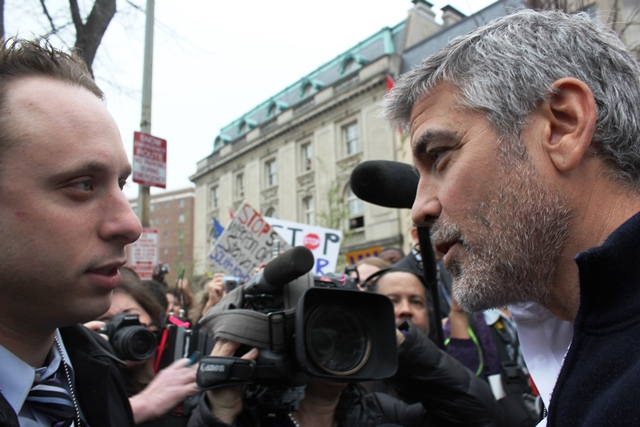George Clooney speaks to a reporter as he arrested for trespassing at the Embassy of Sudan in Washington, DC, 2012.
