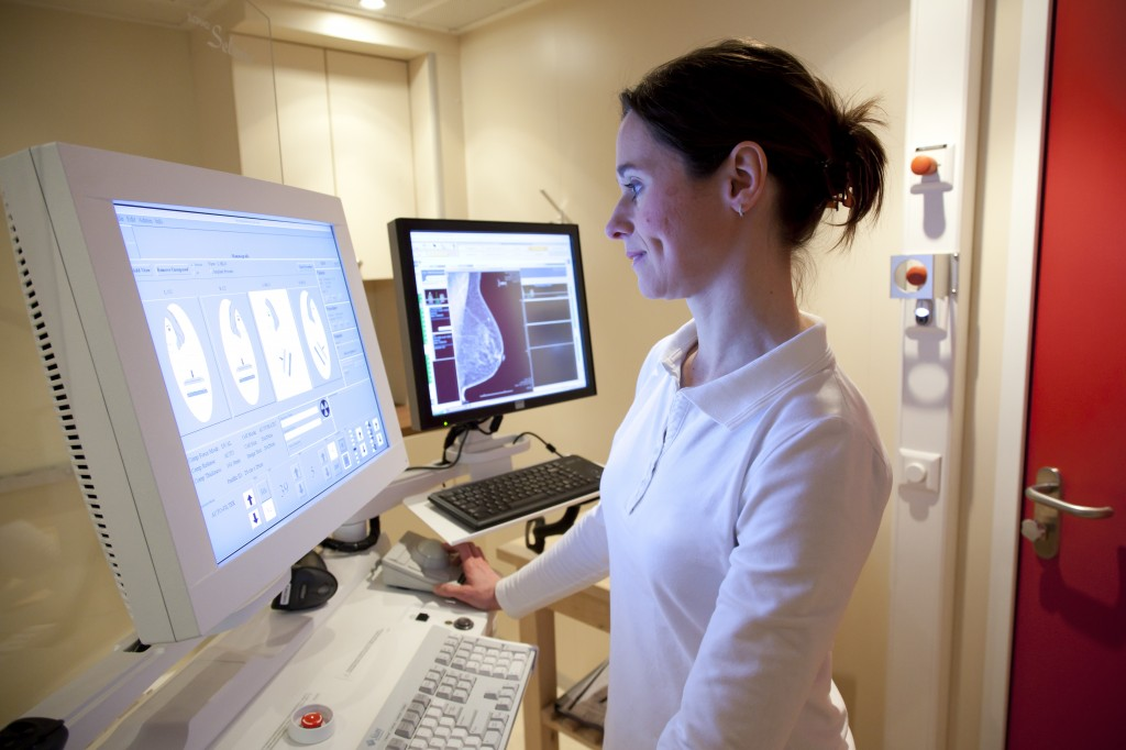 Radiology technician performing mammography scan