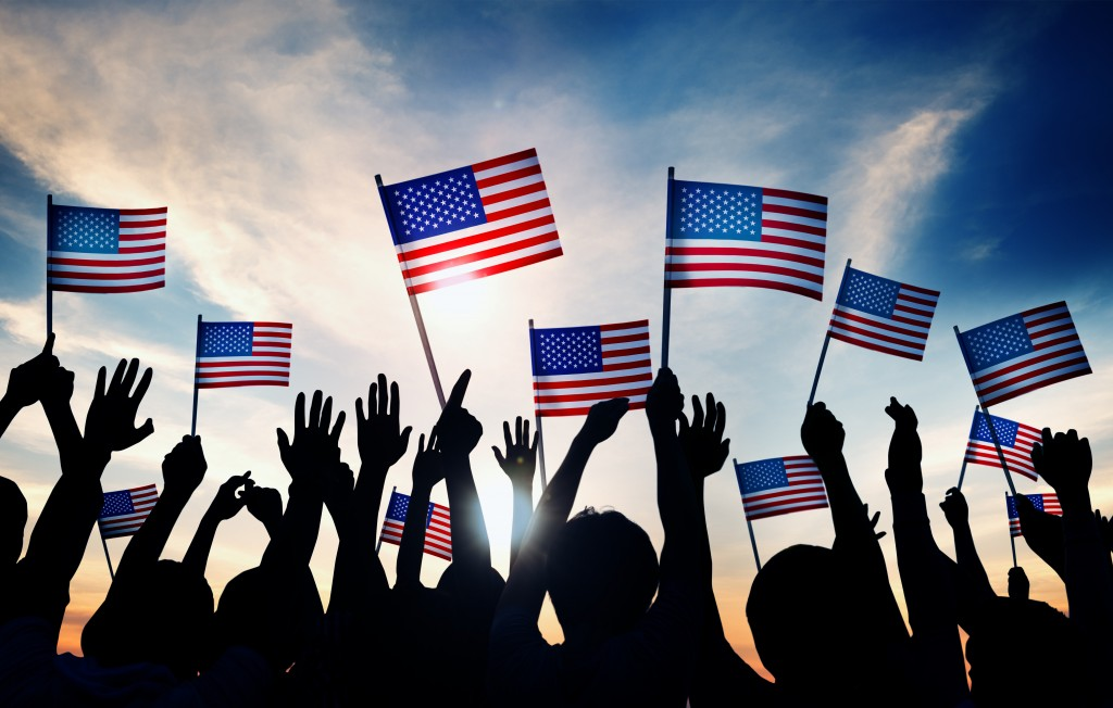 Group of People Waving American Flags in Back Lit