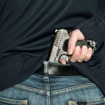 A person is hiding a handgun under the denim belt.