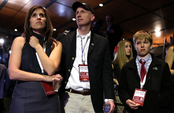 Nancy French, husband David, daughter Camille (13) and son Austin (11) react to the election results displayed on a television during Mitt Romney's campaign election night event at the Boston Convention & Exhibition Center.