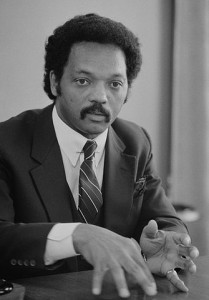 335px-Jesse_Jackson,_half-length_portrait_of_Jackson_seated_at_a_table,_July_1,_1983_edit