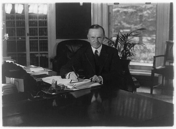 Calvin_Coolidge_seated_at_desk_in_Oval_Office_LOC3b39484r