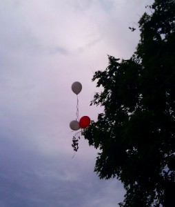 Balloons against cloudy sky and dark tree